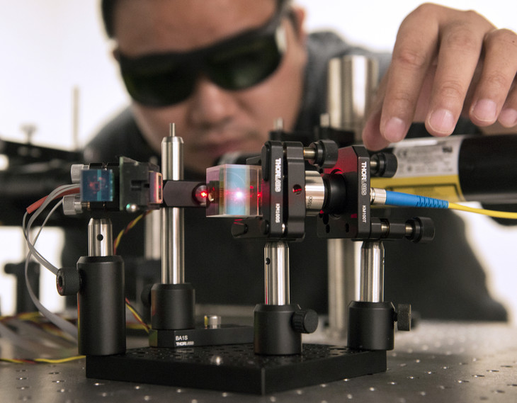 Peng Deng, a postdoctoral fellow in Penn State's School of Electrical Engineering, makes adjustments to the MEMS laser beam optical communication system in his EE East lab.