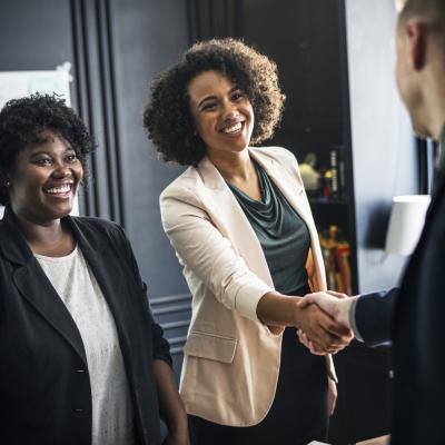 Two women greeting a man